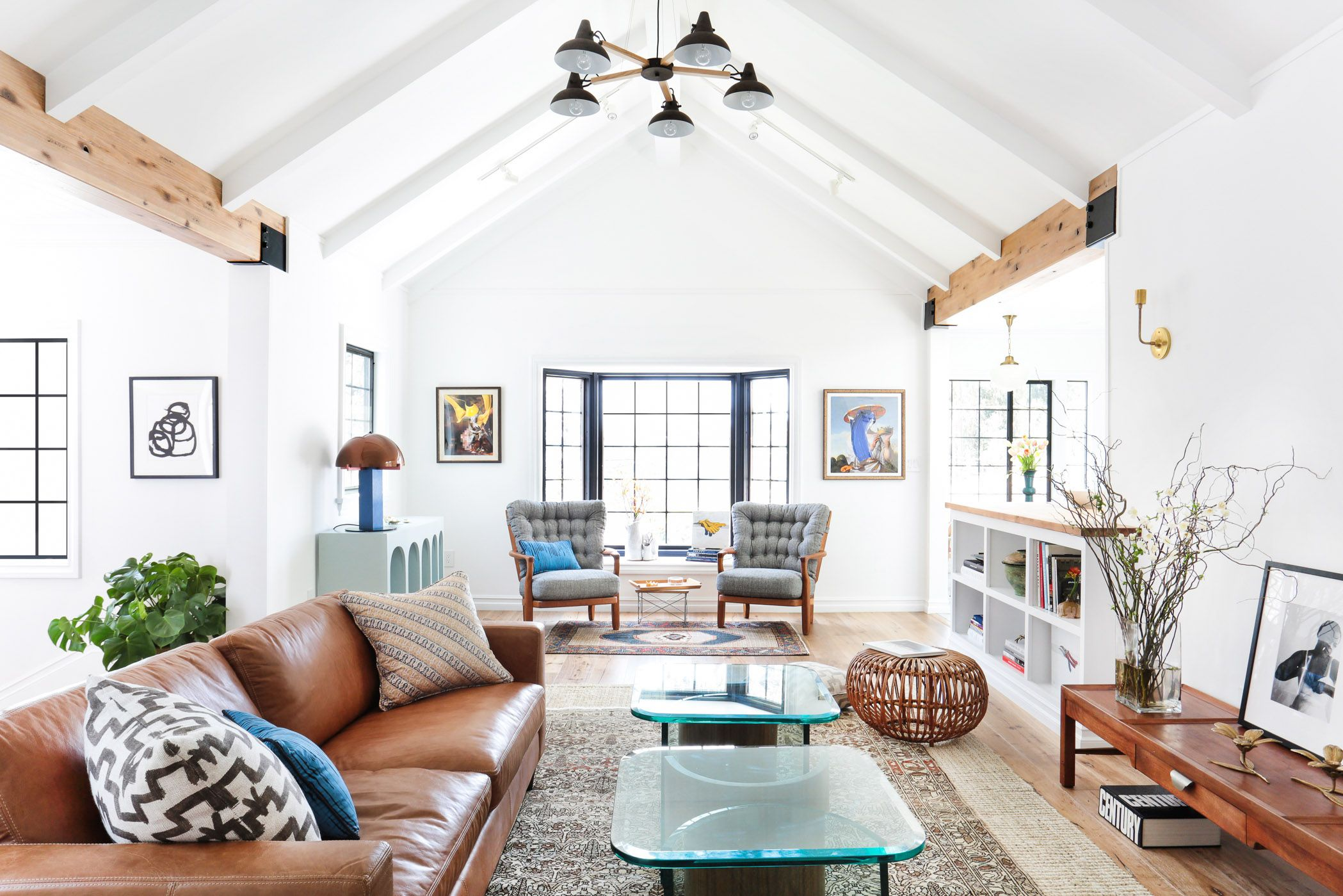 Salon de style scandinave: plafonds clairs avec poutres en bois, grandes fenêtres, parquet et détails bien pensés dans le décor de la pièce (vases, peintures, lampes, pots de fleurs)