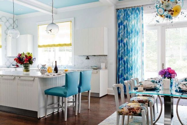 La combinaison de rideaux jaunes romains et de rideaux bleus en mousseline de soie donne à la cuisine un léger esprit romantique