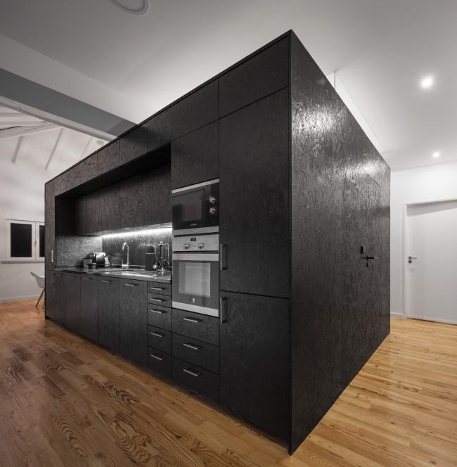 Cuisine et bloc sanitaire à l'intérieur du loft avec murs OSB peints et vernis en noir
