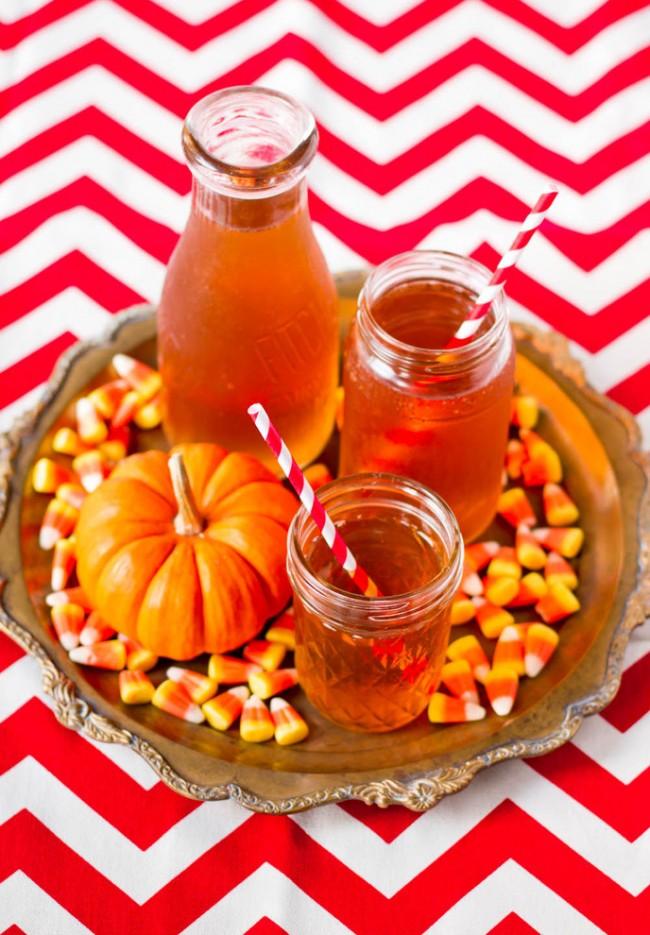 Réglage de la table à la maison.  Le décor automnal de la table à thé est souvent composé de gourmandises: miel, sirops, boissons aux fruits, petites citrouilles et plus encore.