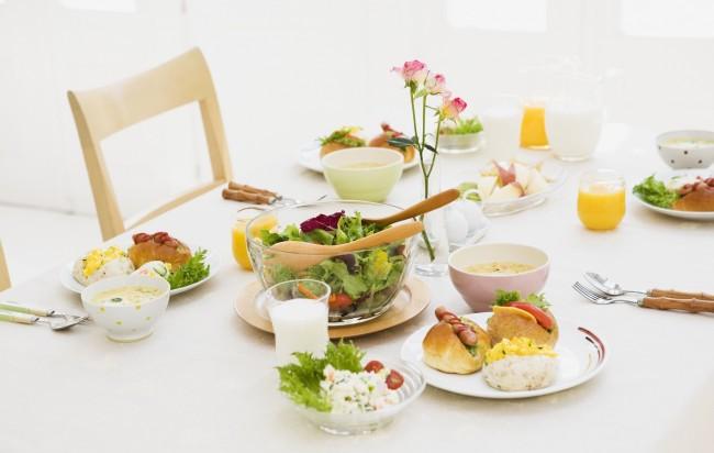 Réglage de la table à la maison.  Table de petit-déjeuner: verrerie simple, couverts en bois et nappe blanche comme neige.  Les fleurs fraîches sont toujours en place, vous pouvez décorer la table du petit-déjeuner avec elles en petites quantités