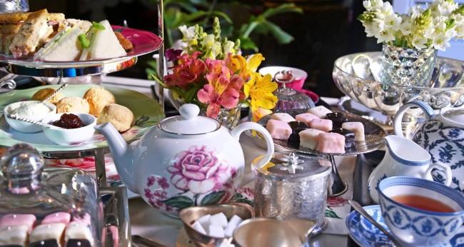 Réglage de la table à la maison.  Un goûter dans le jardin consiste à ne servir que des accessoires de dessert et de petites assiettes.  Les gâteaux sont disposés dans des vases communs