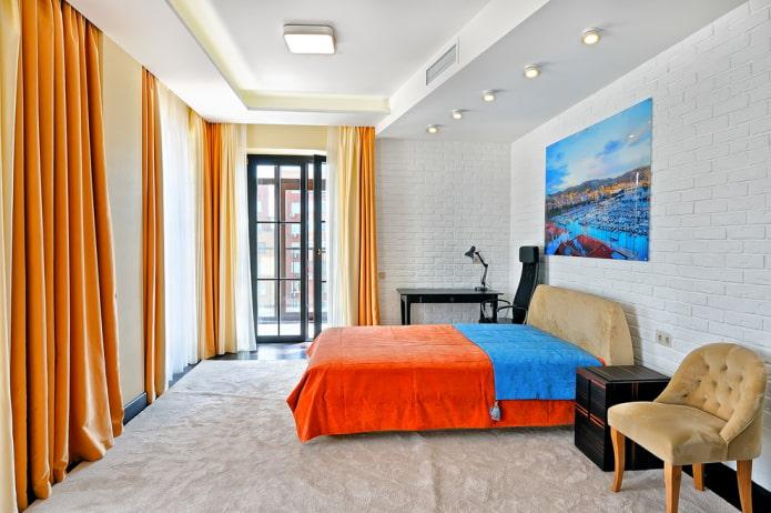 lit avec couvre-lit orange dans la chambre