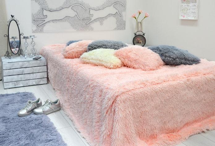 lit avec un couvre-lit dans la chambre
