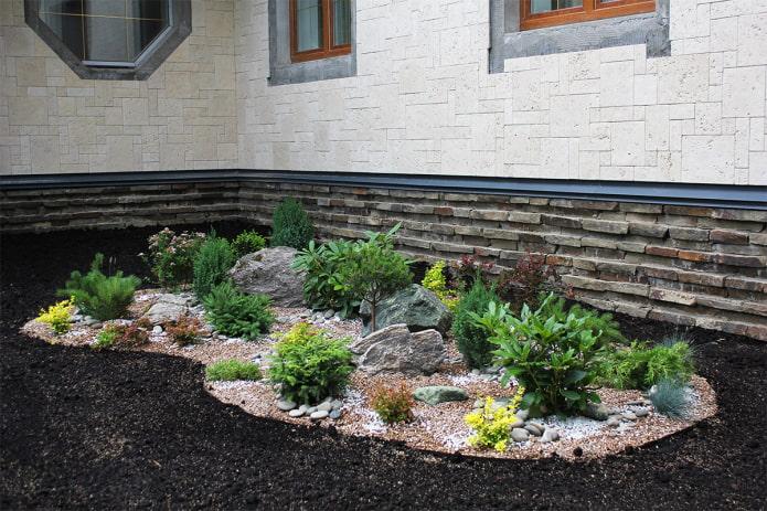 parterre de fleurs avec des pierres près de la maison