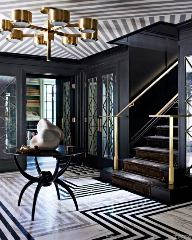 Géométrie au sol et au plafond, couleurs noir et blanc, un lustre inhabituel, un escalier - tout cela donne le style art déco