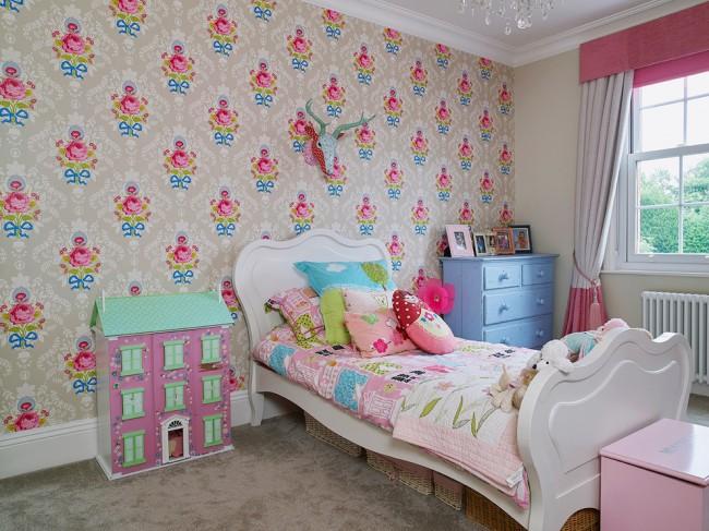 Le mur avec le lieu de couchage est mis en valeur avec du papier peint avec des roses lumineuses sur un fond neutre.