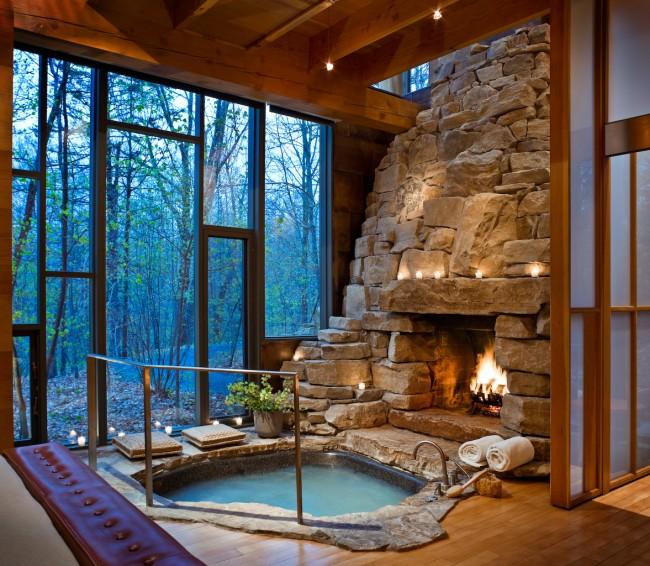 Baignoire encastrée luxueuse sous une paroi de verre offrant une vue sur la forêt.  C'est tellement confortable à tout moment de l'année grâce à la cheminée avec feu vivant à proximité
