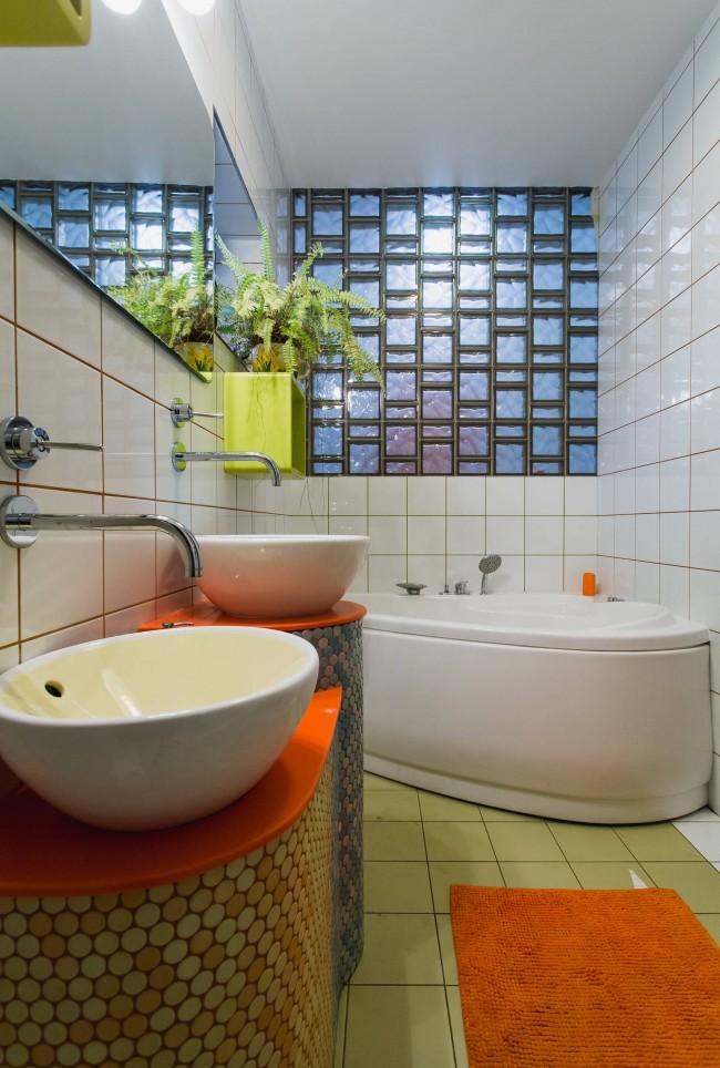 Une petite salle de bain moderne, où une cloison transmettant la lumière en blocs de verre sert de décor sur une police acrylique d'angle