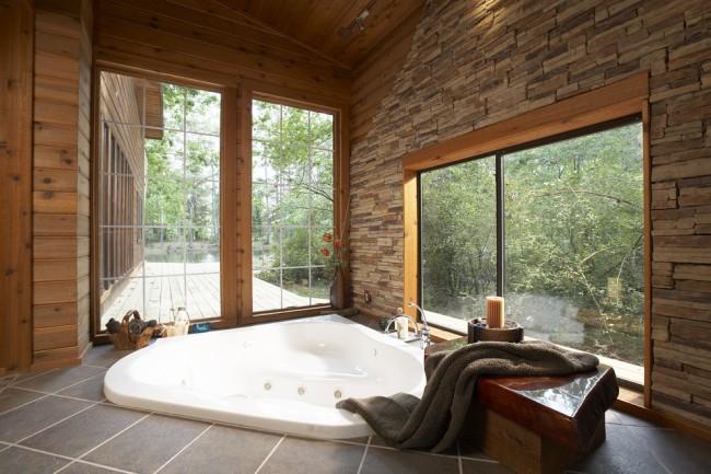 La baignoire intégrée sous les fenêtres panoramiques est très belle