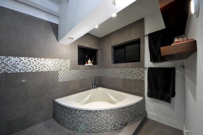 Une belle combinaison de mosaïques sur les murs et dans la paroi de la baignoire