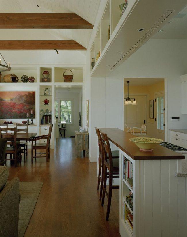 Cuisine de style classique avec comptoir de bar en bois.  Configuration de construction murale.  Projecteurs au-dessus de la salle à manger, les piliers intégrés à la console