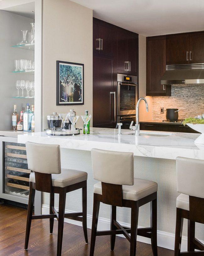 Plusieurs fonctions remplies par le comptoir du bar en même temps: poste de travail supplémentaire, division de la cuisine en plusieurs zones, salle à manger compacte