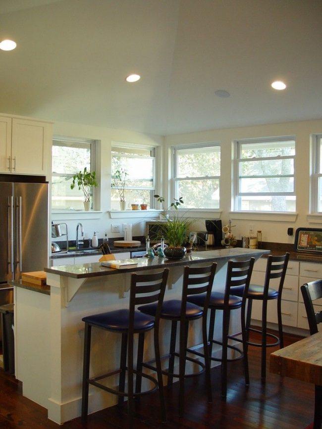Comptoir de bar pour une cuisine à deux niveaux.  Une moitié, haute, sert de table à manger, et l'autre de lieu de travail supplémentaire
