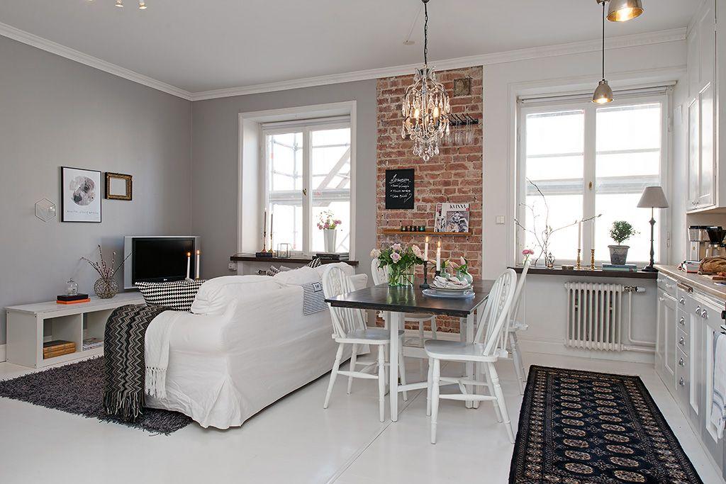 Un mur de briques sépare visuellement le salon de la cuisine
