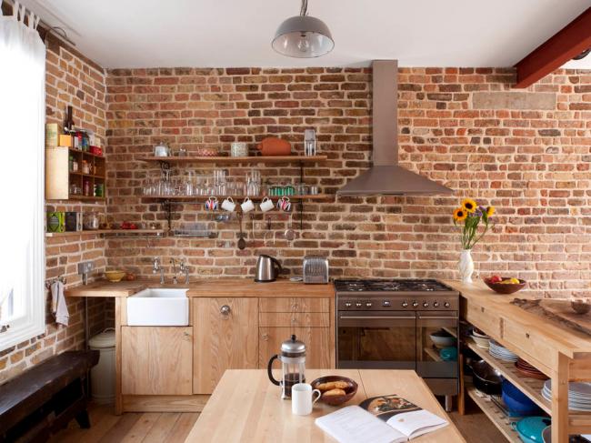 Petite cuisine avec murs de briques sans armoires supérieures