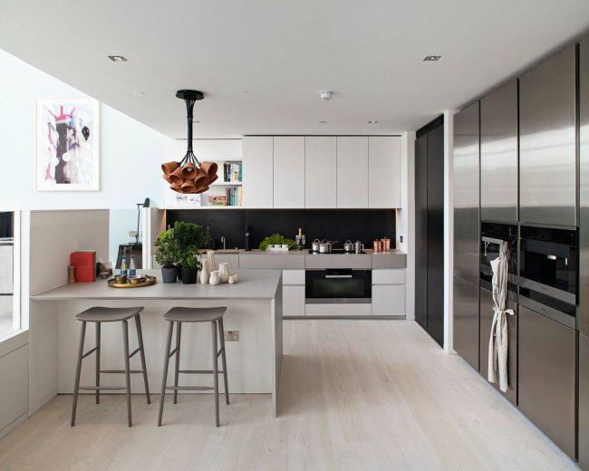 Cuisine spacieuse de style scandinave avec une abondance d'armoires et d'appareils encastrés