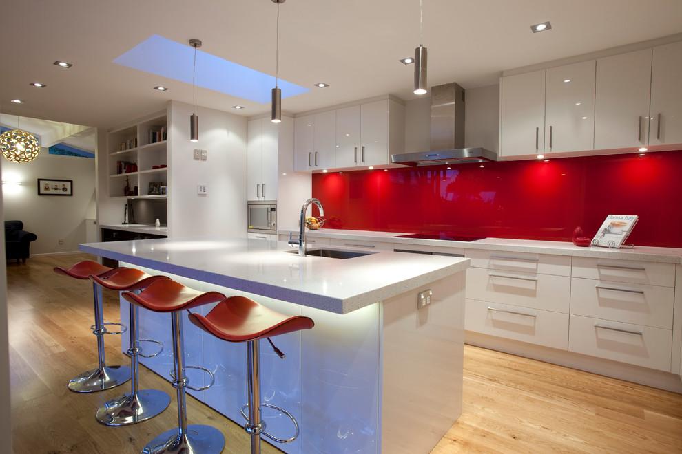 Un tablier de cuisine rouge sur fond de meubles blancs est très impressionnant