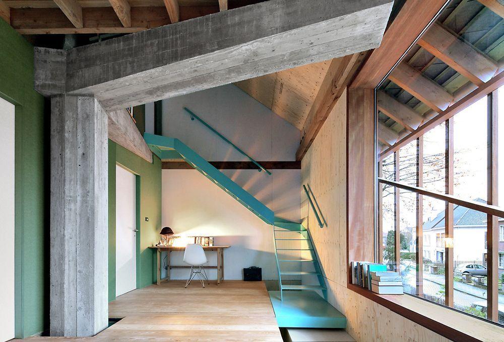 Excellente combinaison de sols en béton nu, d'escaliers en bois et en métal turquoise