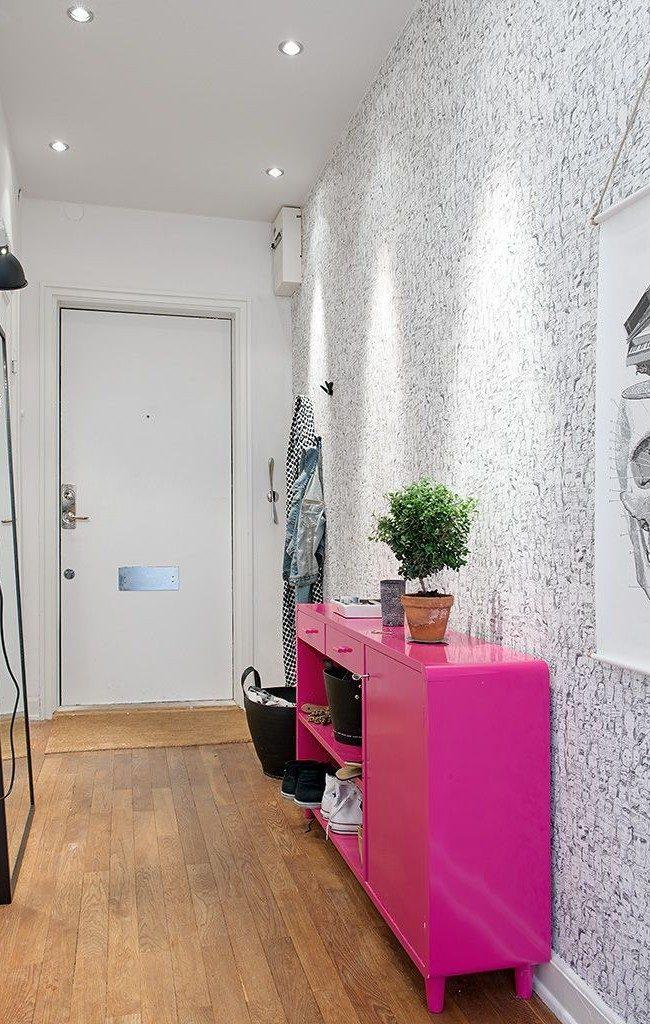 Couloir étroit et lumineux avec une commode lumineuse accentuée et un éclairage multipoint