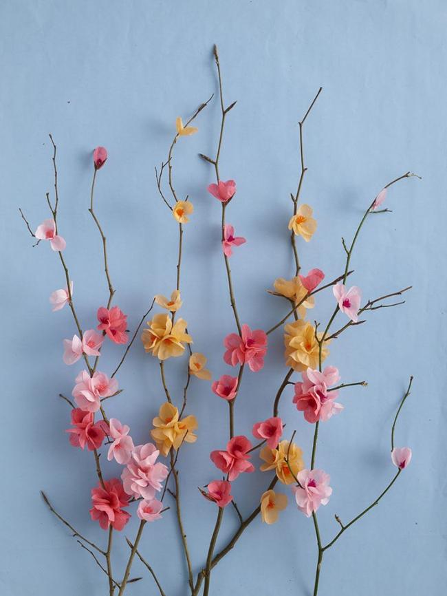 Petites fleurs en papier sur une brindille