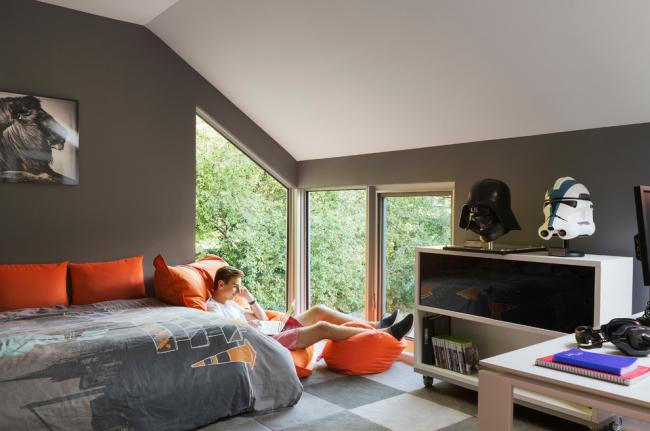 Une chambre d'adolescent avec un coin salon confortable près de la fenêtre