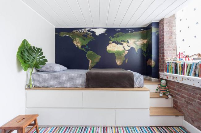 Chambre élégante pour un garçon avec une carte du monde sur l'un des murs au lieu de papier peint et un lit sur le podium