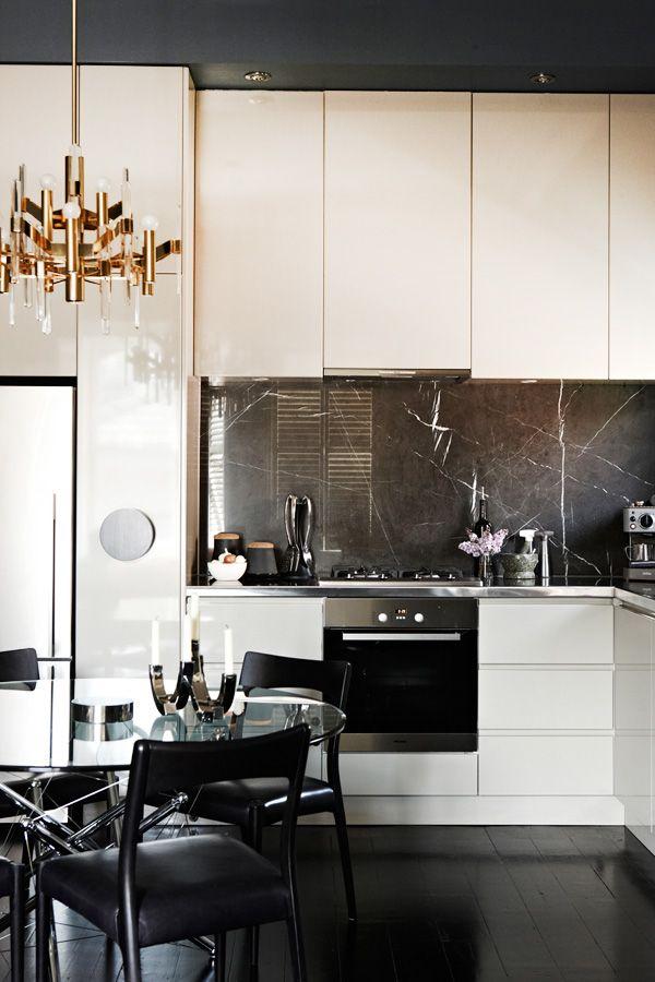 Un intérieur sophistiqué créé avec seulement deux couleurs de base et une paire d'accents - un dosseret en marbre noir et un éclairage suspendu dans le plus pur style Art Nouveau