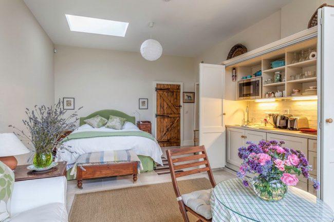 La solution idéale pour un petit appartement d'une pièce sera les portes qui cachent la cuisine dans le placard.