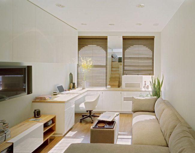 Appartement d'une pièce avec un canapé d'angle moelleux, qui est un lieu de couchage en même temps