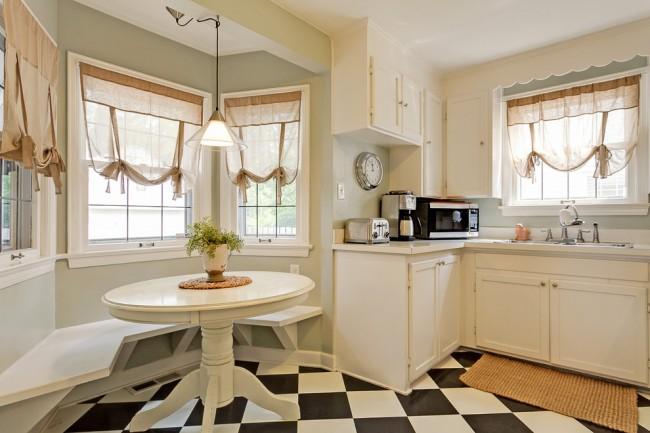 Les rideaux beige clair avec des liens ont fière allure avec une cuisine laiteuse