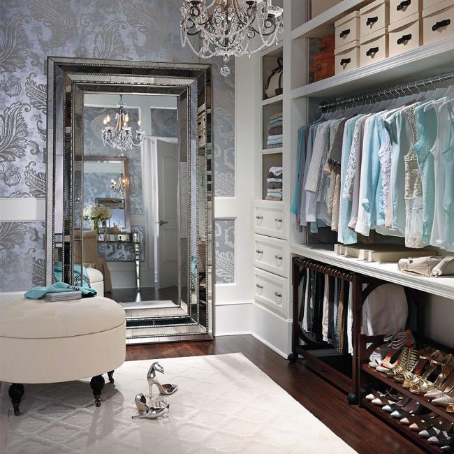 Dressing classique avec espace de rangement pour diverses choses avec un grand miroir et un pouf rembourré