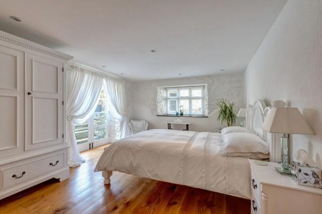 Chambre lumineuse dans un style classique avec des rideaux translucides blancs