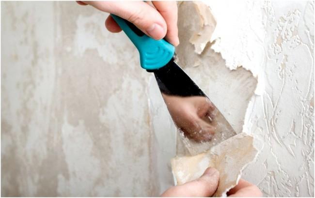 Travailler avec une spatule pour préparer les murs à coller