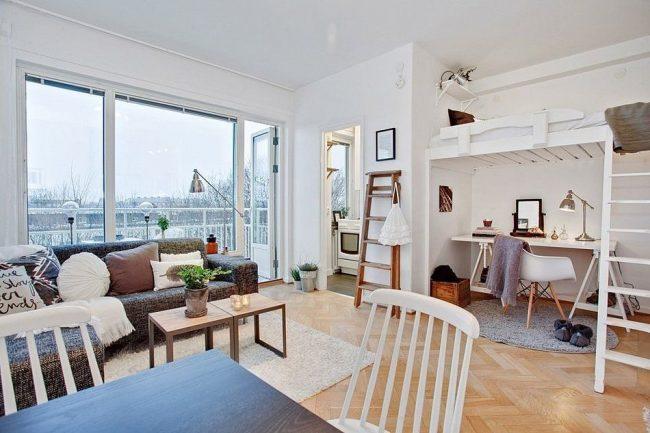 Style scandinave dans la conception d'un appartement d'une pièce avec un couchage sous le plafond
