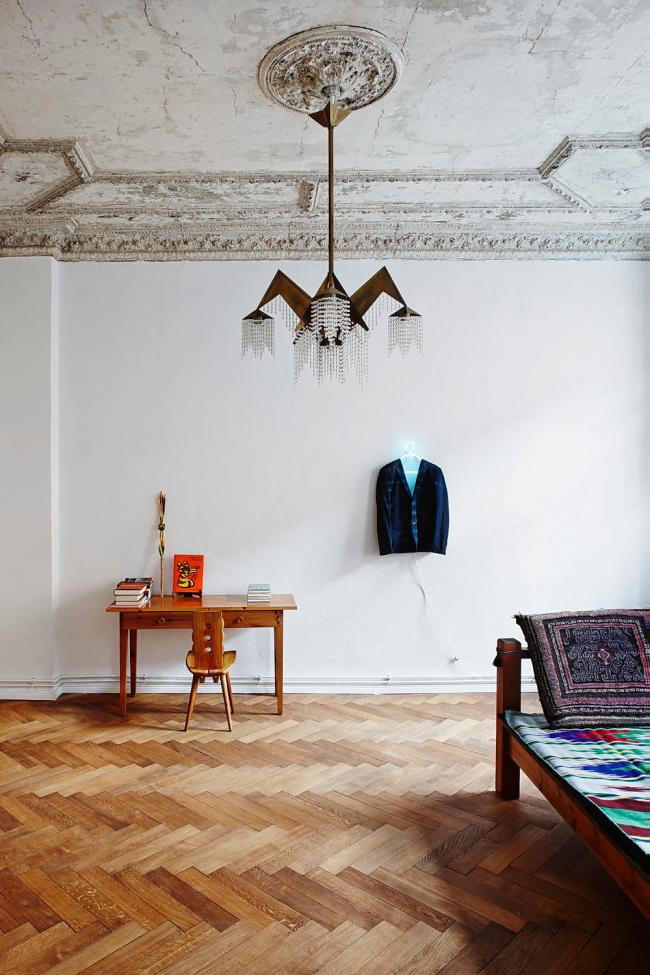 Un lustre avant-gardiste dans un décor classique: plafond vieilli avec stuc, murs blancs neutres, parquet
