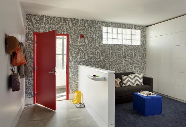 Le papier peint gris sur l'un des murs du couloir est assez moderne en combinaison avec une porte rouge vif.