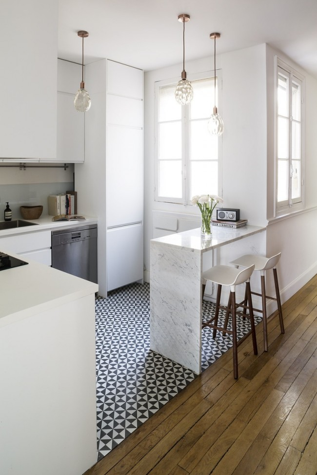 Petits carreaux noirs et blancs dans une cuisine lumineuse zonant parfaitement l'espace de travail