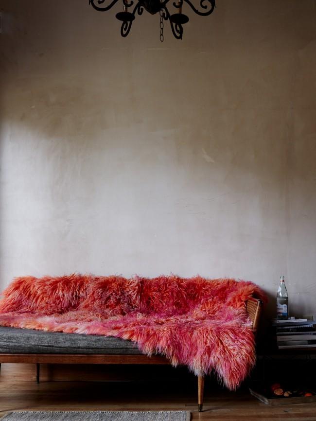 Cape d'accent lumineux en fausse fourrure rouge dans un décor loft sur un canapé en denim