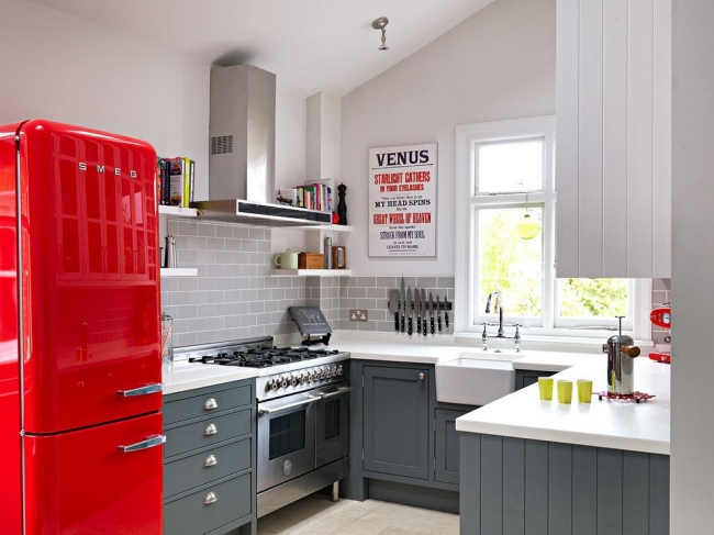 Un tablier de cuisine gris avec imitation de briques, un ensemble gris avec un comptoir blanc, un éclat métallique d'appareils électroménagers - un design simple et fonctionnel qui met en valeur les éclaboussures lumineuses.  Le réfrigérateur rétro rouge est un élément unique à l'intérieur de la cuisine