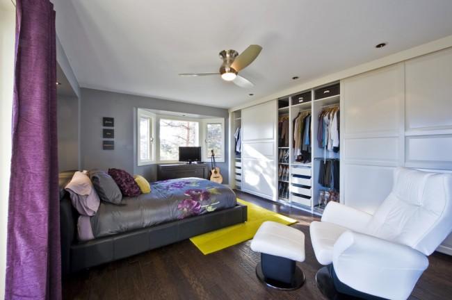 Une armoire spacieuse pour tout le mur dans une grande chambre remplace presque complètement un dressing séparé