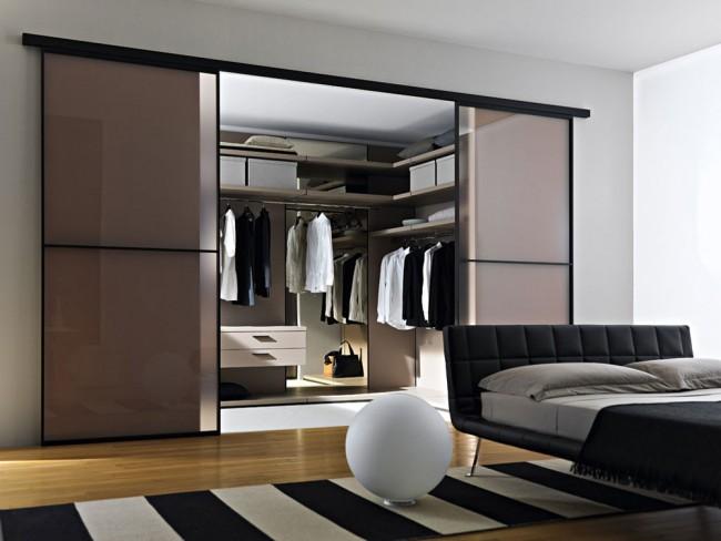 A mi-chemin entre une penderie et un dressing séparé : des portes à enroulement qui séparent une grande niche avec son propre éclairage de la chambre