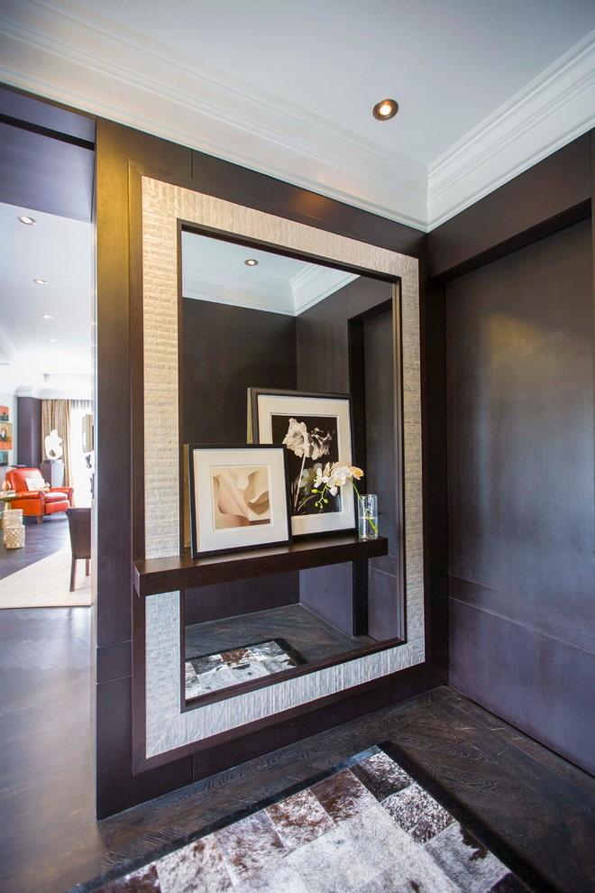 miroir avec une étagère à l'intérieur du couloir