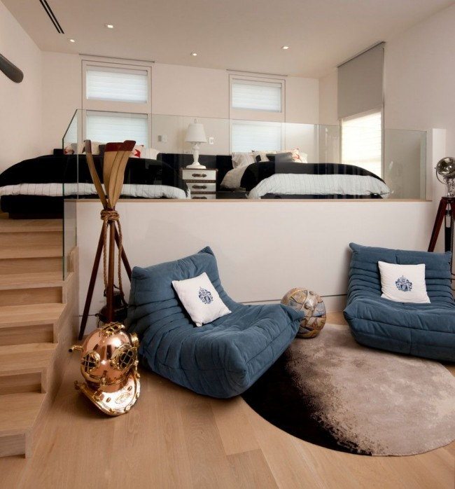 Des lits sur un podium élevé avec des marches dans un intérieur contemporain élégant.  Ainsi, l'effet décoratif d'un escalier à part entière est créé ici et les rampes en verre complètent l'impression.