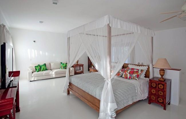 Le baldaquin au-dessus du lit peut non seulement s'intégrer harmonieusement dans n'importe quel intérieur, comme le mobilier du milieu du XXe siècle sur la photo, mais remplira également un certain nombre de fonctions utiles