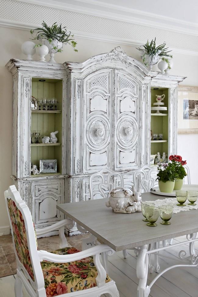 Belle garde-robe antique dans la salle à manger.  Remarquez comment les riches couleurs du rembourrage contrastent magnifiquement avec le blanc.