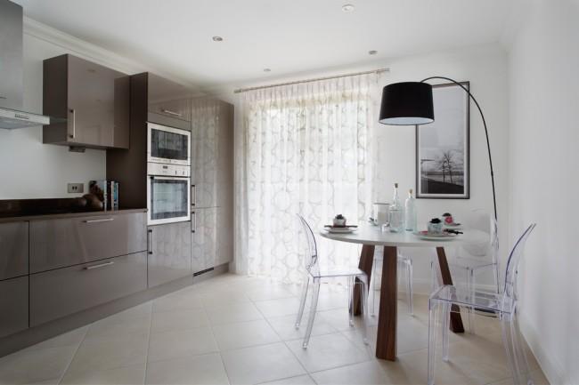 Design discret de la cuisine aux couleurs neutres et rideau transparent à motif géométrique