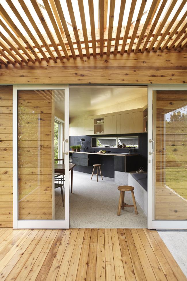 Les portes coulissantes en verre aérées sont en parfaite harmonie avec la décoration de la maison en bois naturel