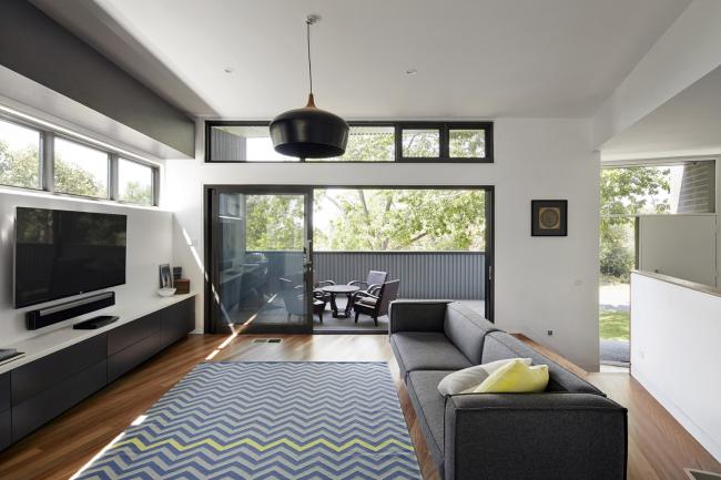 Salon spacieux d'une maison privée avec une porte vitrée qui mène à un espace de détente confortable dans la cour