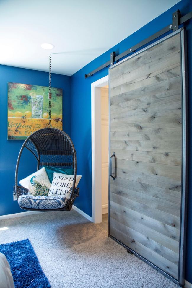 La porte coulissante avec une feuille de bois grisâtre est en parfaite harmonie avec la couleur bleu vif des murs de la pièce